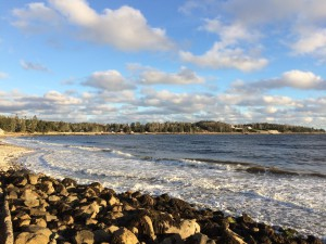 A scenic photo of Cleveland Beach with rocks and blue sky with clouds